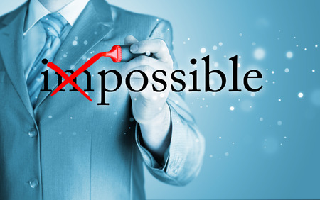 difficult mission: Businessman Hand turning the word Impossible into Possible with red marker