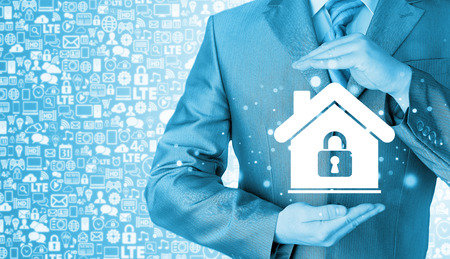 protect home: Businessman protect a house, home lock concept.