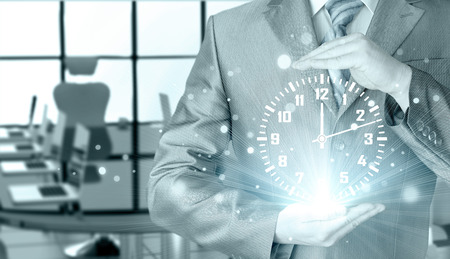 against the clock: businessman holding clock against illustration background