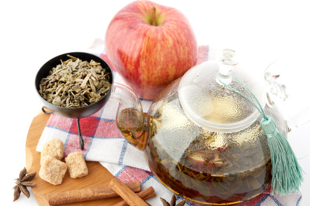 barbarum: Ripe apple, cinnamon and fruit drink in glass teapot on white background Stock Photo
