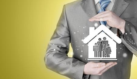 prosperidad: hombre de negocios la protecci�n de la familia en casa con las manos Foto de archivo