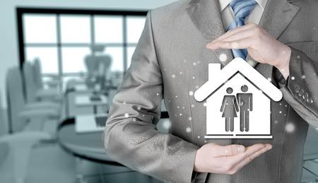 zakenman beschermen familie in huis met handen Stockfoto