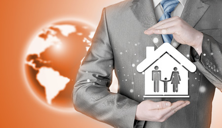 wealth concept: businessman protecting family in home with hands