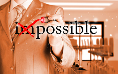 business problems: Businessman Hand turning the word Impossible into Possible with red marker