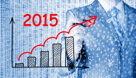 upturn: business man drawing growth graph for year 2015