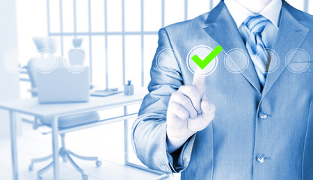 voting box: business man touching, pressing modern button with green ticking Check Box. Stock Photo