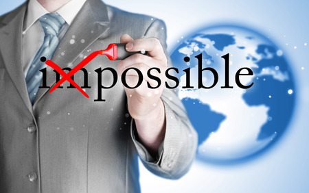 business change: Businessman Hand turning the word Impossible into Possible with red marker