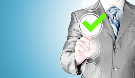 electing: business man touching, pressing modern button with green ticking Check Box. Stock Photo
