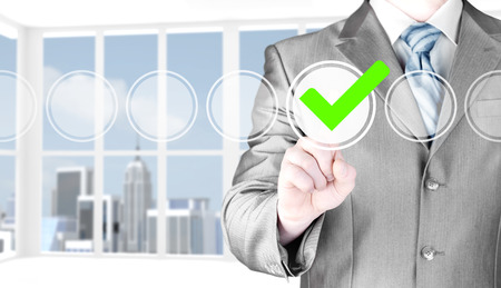 business decisions: business man touching, pressing modern button with green ticking Check Box. Stock Photo