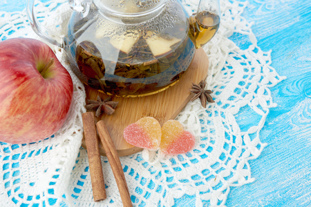 barbarum: Ripe apple, cinnamon and fruit drink in glass teapot on wooden background