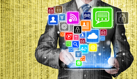business media: Business man using tablet PC with social media icon set