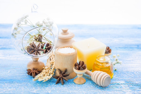 body conscious: spa treatment -  star anise, honey, salt, arranged with soap bar, pebbles and towels on wood