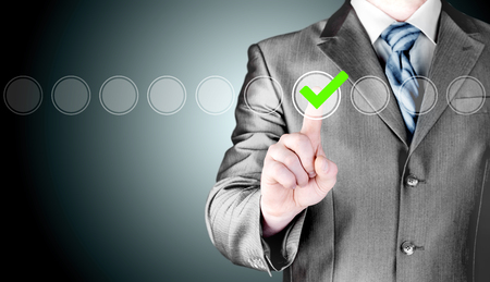 list: business man touching, pressing modern button with green ticking Check Box. Stock Photo