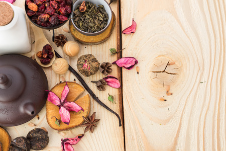 pile of leaves: dry tea leaves cinnamon and on wooden background