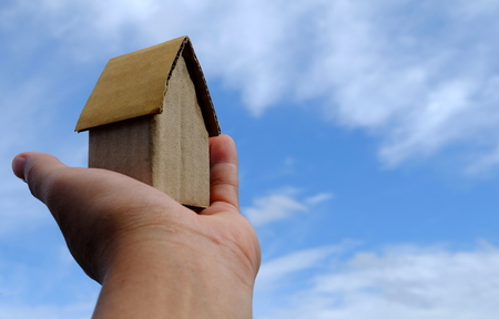 Cardboard House in Hand with Blue Sky Background.