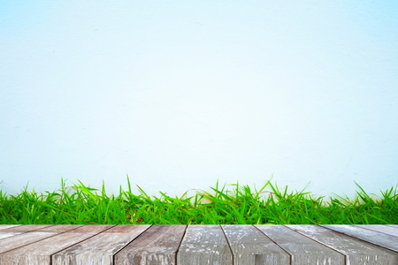 Empty Wooden Table with Green Grass and Concrete Background, Suitable for Presentation, Web Temple, Backdrop, and Product Display.