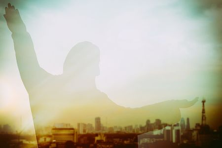 Abstract Double Exposure of Jesus Silhouette with Cityscape Background and Light Leak.