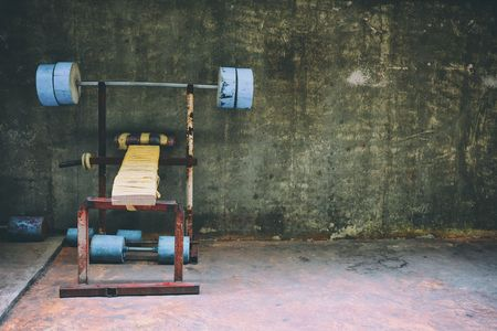 Homemade Barbell Bench in Concrete Room Background.