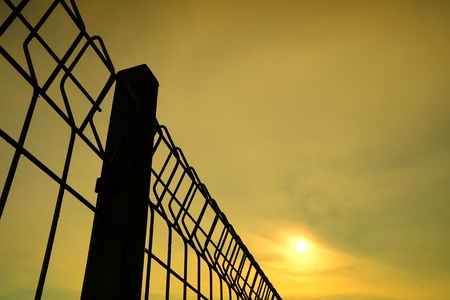 Silhouette of Steel Fence with Sunset Background.