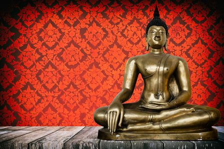 Ancient Buddha Image on Wooden Table with Ancient Vintage Thai Mural on Wall Background, Using Buddhist Religion Concept. Stock Photo