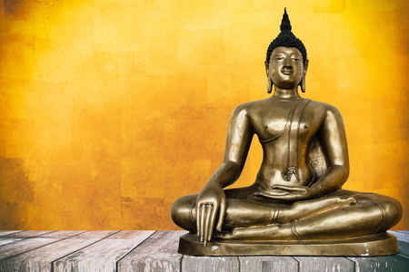 Ancient Buddha Image on Wooden Table with Gold Leaf Texture Background, Using Buddhist Religion Concept. Stock Photo