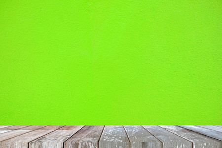 Empty Wooden Table with Green Painted Concrete Background, Suitable for Presentation, Web Temple, Backdrop, and Product Display. Stock Photo
