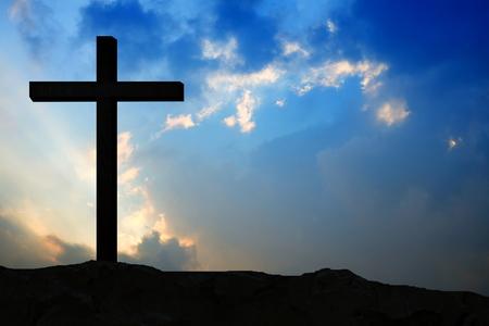Hölzernes Kruzifix von Jesus auf dem Berg mit Sonnenunterganghintergrund für katholische und christliche Religionskonzepte. Standard-Bild