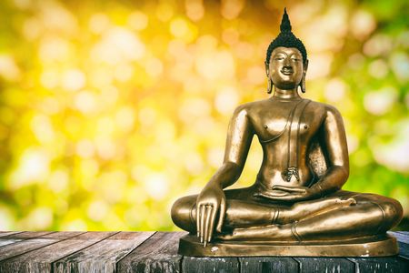 Ancient Buddha Image on Wooden Table with Bokeh Background, Using Buddhist Religion Concept. Stock Photo