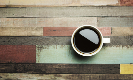 Top angle cup of coffee with color wooden background Foto de archivo