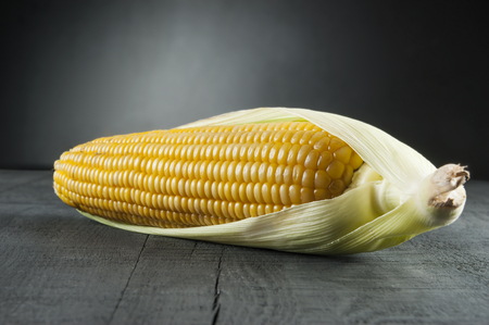 boiled corn with leaf on black backdrop and background