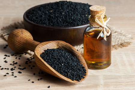 Black cumin seeds in bowl. Nigella Sativa in glass bottle. Organic herbal medicine
