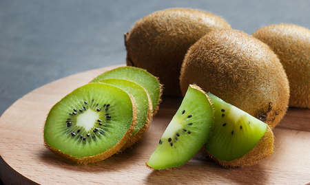 Juicy kiwi on wooden background Banco de Imagens