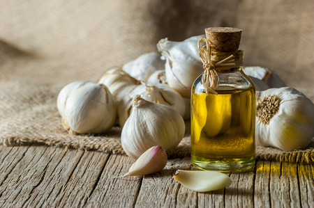 Ripe and raw slices of garlic on wooden table. Garlics background