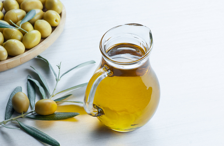 Glass of olive oil on a white background. green olives background, olivae oleum