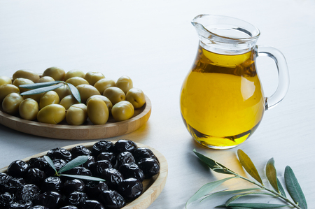 Green olive leaves in glass and bottle on white background. olives background, olivae oleum