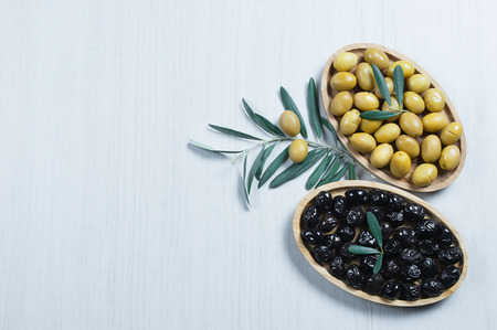 green and black olive leaves in bamboo bowl. olives background, olivae oleum