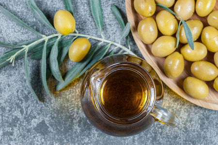 Green tea leaves in glass on wooden table. olives background, olivae oleum Фото со стока