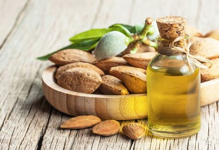 Glass bottle of almond oil and almond nuts on wooden background