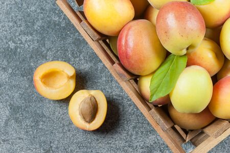 Fresh whole Ripe apricot fruits with a leaf and half in wooden basket on gray rustic table. Apricots healthy fruit background