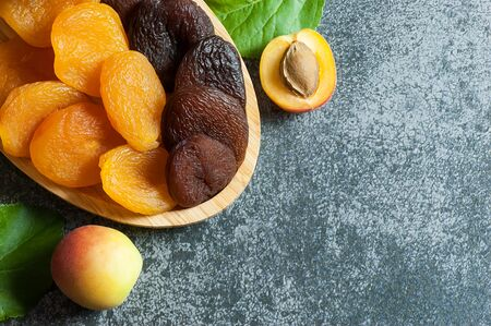 Natural dried apricots with fresh whole Ripe apricot and half in bamboo bowl on gray rustic table, dry apricot fruits healthy food