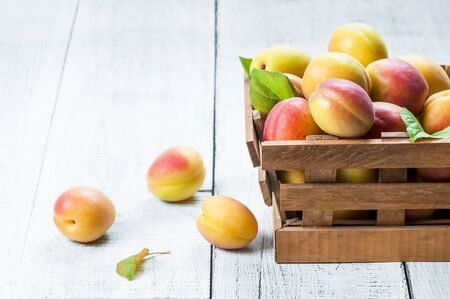 Fresh whole Ripe apricot fruits on a wooden table. Apricots healthy fruit background Imagens
