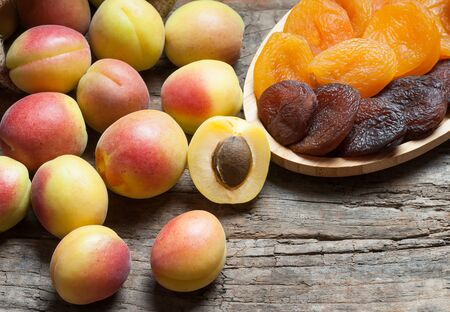Natural dried apricots in bamboo bowl with fresh whole Ripe apricot on wooden rustic backdrop, dry apricot fruits healthy food background