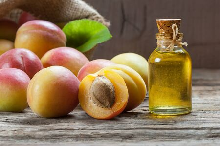 Glass bottle of apricot seed kernel oil (prunus armeniaca oleum) with fresh ripe apricot fruits on wooden rustic background Imagens