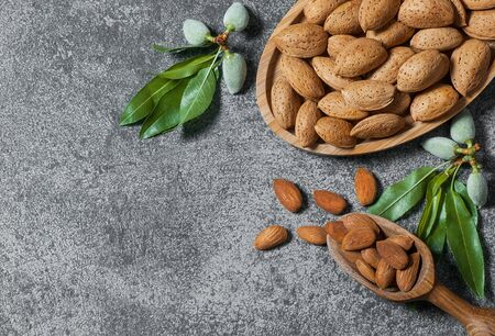 Top view of almond nuts on wooden table. Almond background with copy space