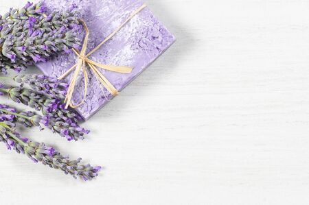 Lavender natural soap with fresh lavender flowers on white rustic table, aromatherapy spa massage concept