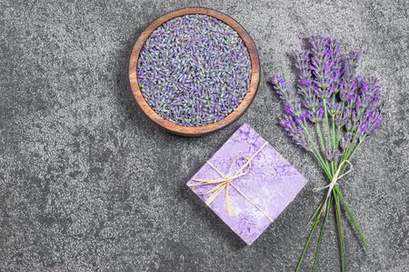 Lavender natural soap with fresh lavender flowers and dried lavender seeds on gray rustic table, aromatherapy spa massage concept