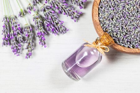 Glass bottle of Lavender essential oil with fresh lavender flowers on white rustic table, aromatherapy spa massage concept. Lavendula oleum Imagens