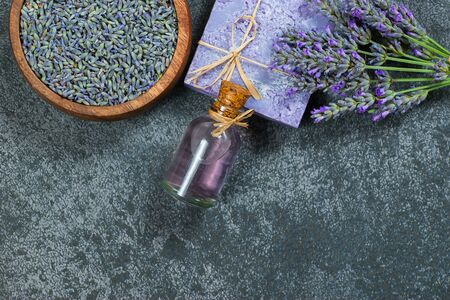 Lavender natural soap and lavender oil with lavender flowers and dried lavender seeds on gray rustic table, aromatherapy spa massage concept. Lavendula oleum Imagens