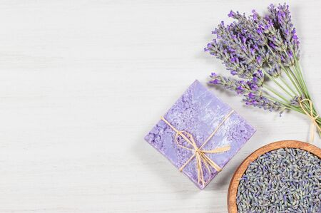 Lavender natural soap with fresh lavender flowers and dried lavender seeds on white rustic table, aromatherapy spa massage concept