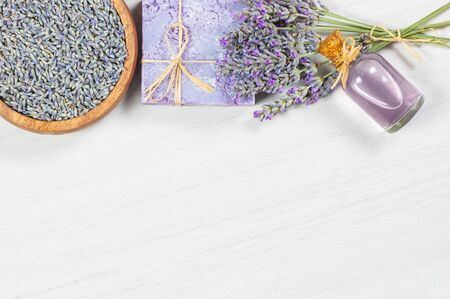 Lavender natural soap and lavender oil on white rustic table, aromatherapy spa massage concept. Lavendula oleum